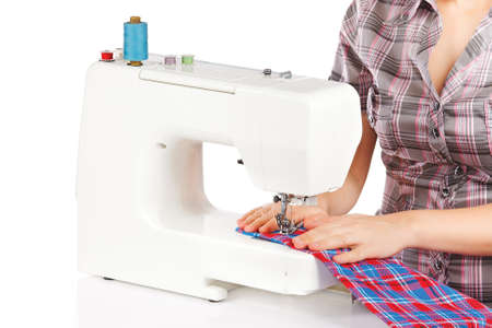 Woman is sewing on the sewing machine on a white background Stock Photo - 12504592