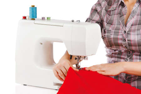 La mujer est� cosiendo en la m�quina de coser sobre un fondo blanco photo