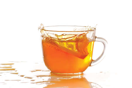 Cup of ice tea and lemon with splash on a white background photo