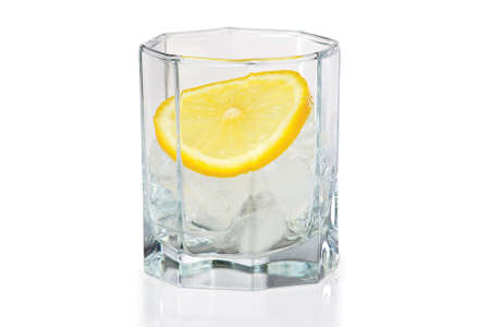 Glass with ice and slice of fresh lemon on a white background photo