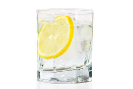 Glass of water, ice and slice of fresh lemon on a white background