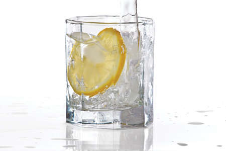 Glass of water, ice and slice of fresh lemon with splash on a white background