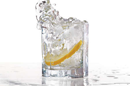 gin: Glass of water, ice and slice of fresh lemon with splash on a white background