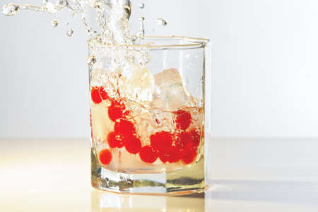 Glass of water, ice and red cranberries with splash in yellow light photo