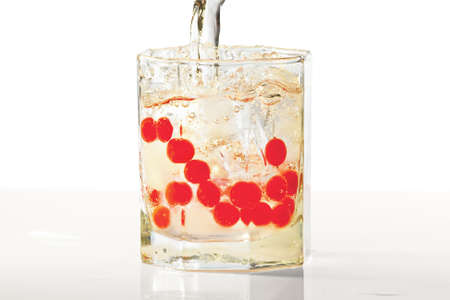icecube: Glass of water, ice and red cranberries with splash in yellow light