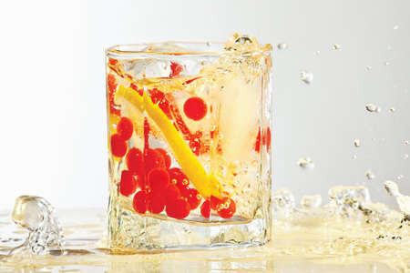 Glass of water, ice, lemon and red cranberries with splash in yellow light photo