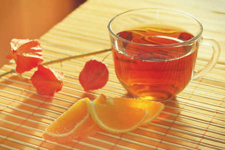 Cup of tea and fruit jelly with physalis on a bamboo table cloth still life photo
