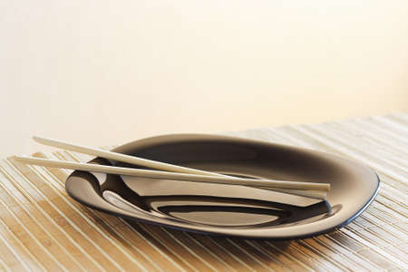 Black dish and chopsticks on a bamboo table cloth still life photo