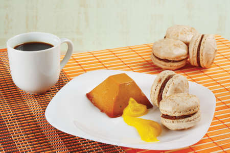 Cup of coffee, macaroons and caramel pudding on a bamboo table cloth still life photo