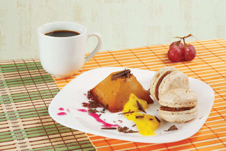 Cup of coffee, macaroons, grapes and caramel pudding still life photo