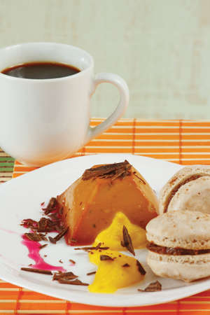 Cup of coffee, macaroons and caramel pudding on a bamboo table cloth still life Stock Photo - 13509478