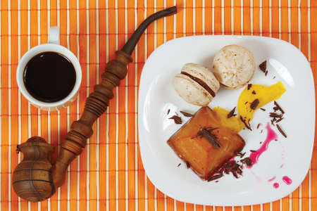 Cup of coffee, tobacco pipe, macaroons and caramel pudding on a bamboo table cloth still life photo