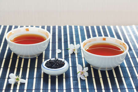 Two cups of tea, jar of tea leaves and cherry blossoms on bamboo table cloth still life photo