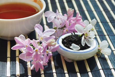 Cup of tea, jar of tea leaves and cherry blossoms with lilac on bamboo table cloth still life Stock Photo