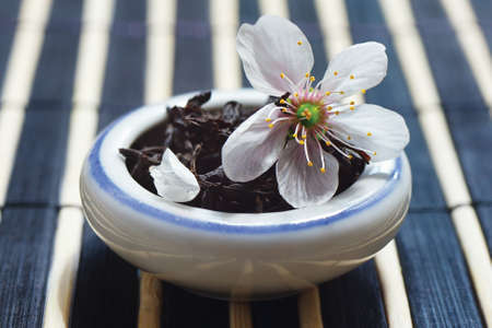 Jar of tea leaves and cherry blossoms on bamboo table cloth still life photo