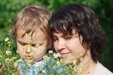 Young mom with her son among the summer daisies outdoors photo