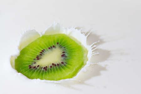 Fresh kiwi falling into the milk with a splash closeup photo
