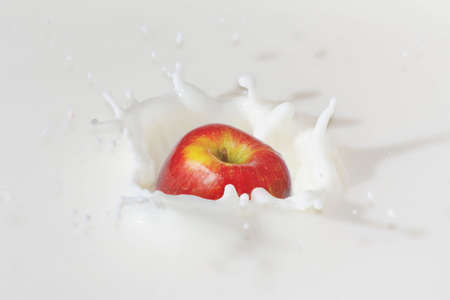 Fresh apple falling into the milk with a splash closeup photo
