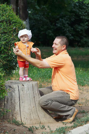Daddy holds little cute daughter by the hand, standing on a stump in the park photo