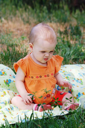 Cute little girl sitting on a meadow Stock Photo - 14123911