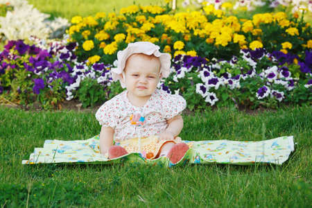 Cute little girl in panama sitting on a flowers meadow photo