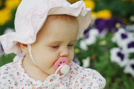 Portrait of a beautiful little girl with a pacifier in panama in the flower background photo