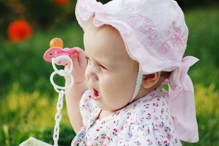Portrait of a cute little girl with a pacifier in panama in the flower background photo