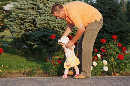 teaches: Father teaches her beautiful little daughter to walk on the background of rose bushes