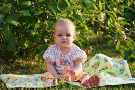 Cute little blonde girl with a pacifier sitting on a meadow photo