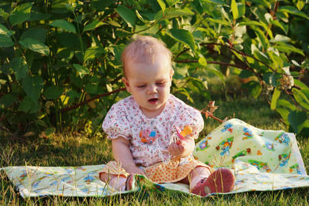 Beautiful little blonde girl with a pacifier sitting on a meadow photo
