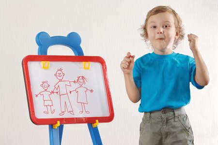 Little smiling boy drew a family on whiteboard photo