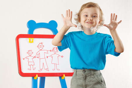 Little smiling cute boy shows his family painted on a whiteboard photo