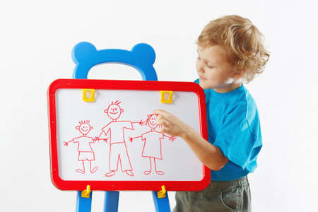 Little cute blond boy shows his family painted on a whiteboard photo