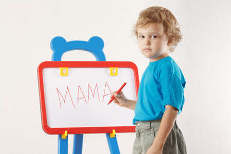 Little cute boy wrote the word mama on whiteboard photo