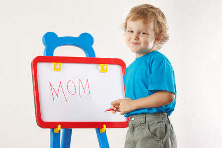 Little cute smiling boy wrote the word mom on whiteboard photo