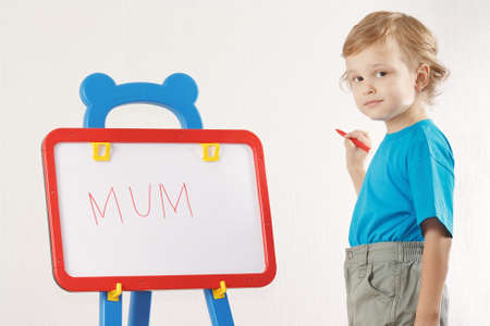 Little cute smiling boy wrote the word mum on whiteboard photo