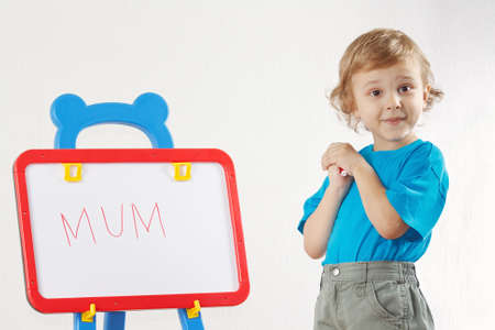 Little cute boy wrote the word mum on whiteboard photo