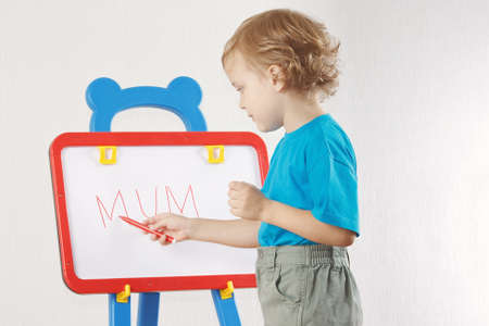 Little cute blond boy wrote the word mum on whiteboard photo