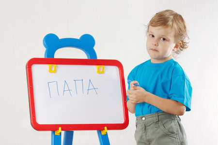 Little cute boy wrote the word papa on whiteboard photo