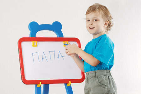 Little cute smiling boy wrote the word papa on whiteboard photo
