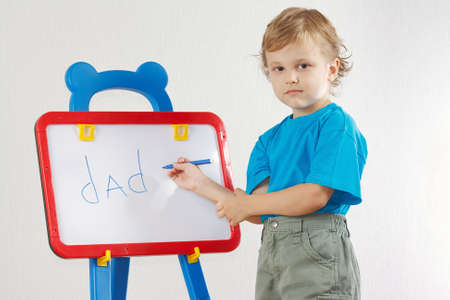 Little cute  boy wrote the word dad on whiteboard photo