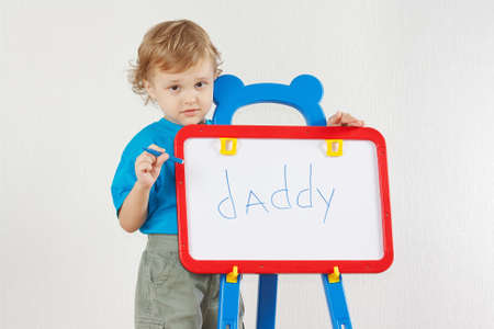 Little cute boy wrote the word daddy on whiteboard photo