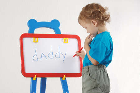 Little cute blond boy wrote the word daddy on whiteboard photo