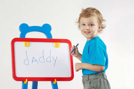 Little smiling boy wrote the word daddy on whiteboard photo