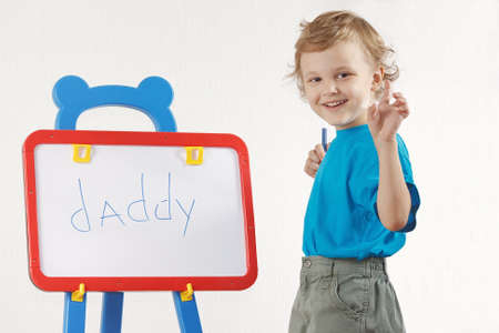 Little cute smiling boy wrote the word daddy on whiteboard photo