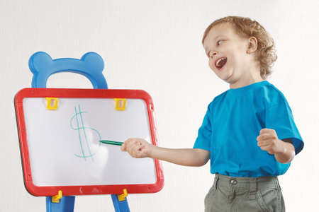 Little cute smiling boy drew a dollar sign on the whiteboard photo