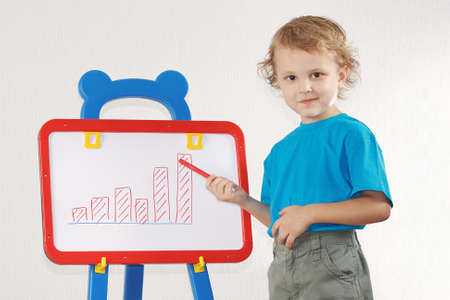 Little cute smiling boy drew a diagram of the growth on the whiteboard photo