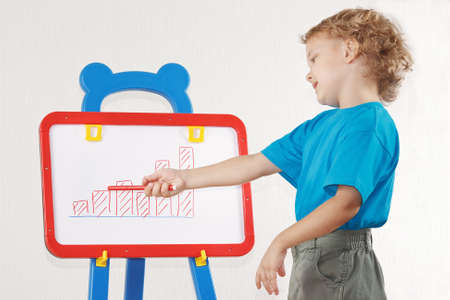 Little blond boy drew a diagram of the growth on the whiteboard photo