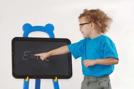 Little cute boy with glasses shows Einstein photo