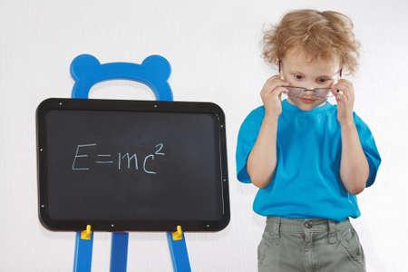 Little amazed boy with glasses shows Einstein photo